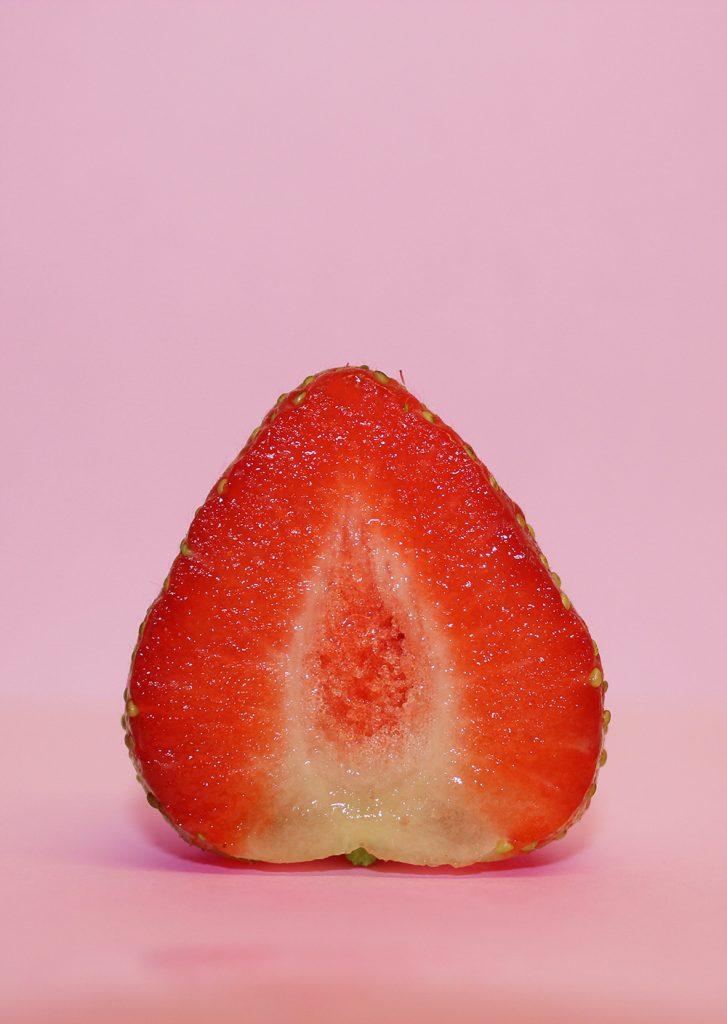 Bauer nebenan Querschnitt einer Erdbeere rosafarbener Hintergrund